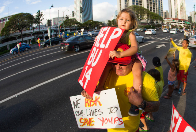 Honolulu lifeguards waved signs in support of their Maui brethren, Monday, at the intersection of Ala Moana Blvd. and Atkinson Drive.