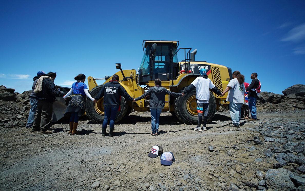 Kahookahi Kunuha leads a small group of supporters near a tractor on the TMT site on the summit of Mauna Kea. 10 april 2015. photograph Cory Lum
