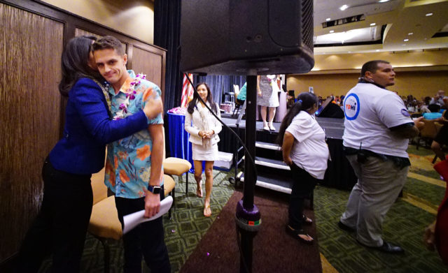 Takai Campaign Mgr Dylan Beesley gets a hug from Congressowoman Tulsi Gabbard after reading a letter from Congressman Takai to the delegates attending the 2nd day of the HI State Democratic Convention. 29 may 2016.
