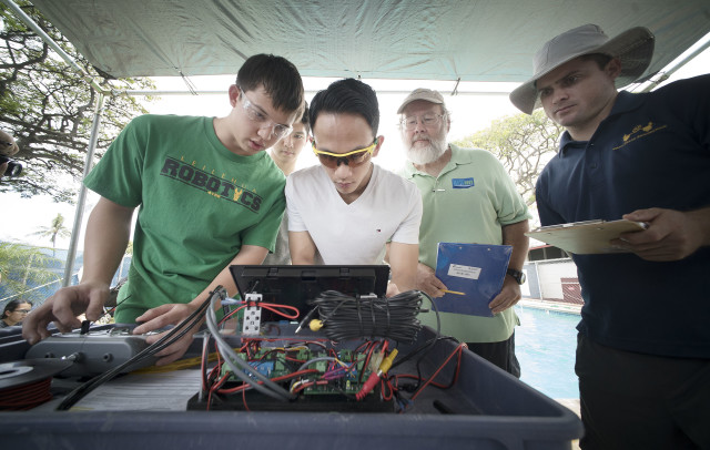 Team from Leilehua High School crowd around their monitor maneuvering their underwater robot with judges monitoring their tasks during the MATE Oahu Regional Competition held at US Coast Guard Base Honolulu. 14 may 2016.