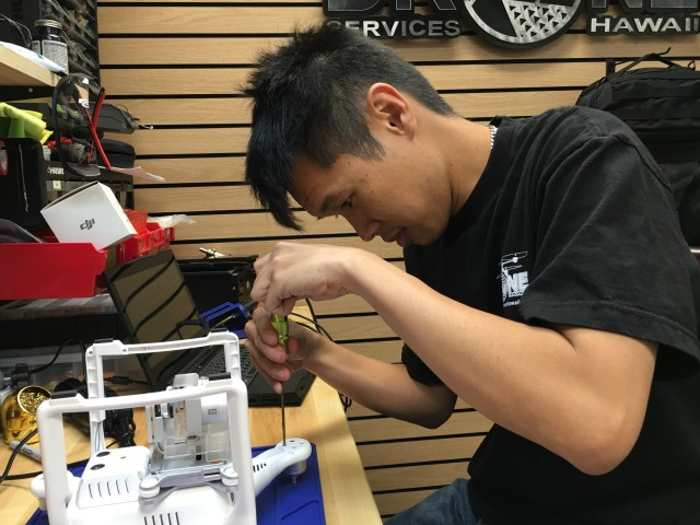 Estin Ma of Drone Services Hawaii completes repairs to the stabilization gimbal of a drone.