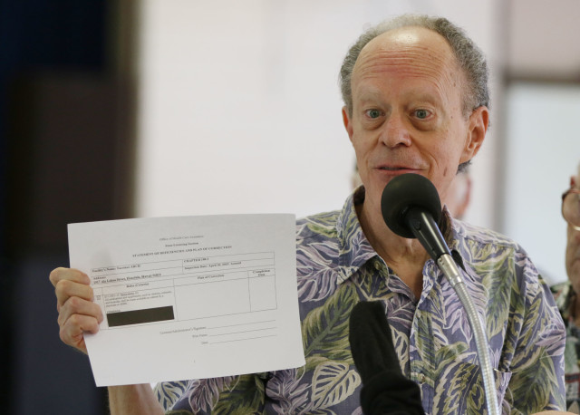 Larry Geller holds up redacted documents during Kokua Council press conference. 25 july 2016