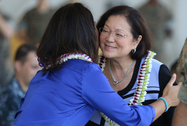 Senator Mazie Hirono receives a kiss/hug from Congresswoman Gabbard before ceremonies opening a new MV22 Osprey hangar at Marine Corps Base Hawaii. 19 july 2016