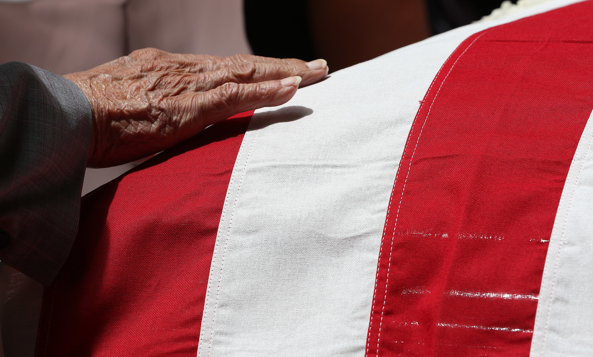<p>A mourner touches the flag atop Takai&#8217;s casket in a gentle farewell.</p>