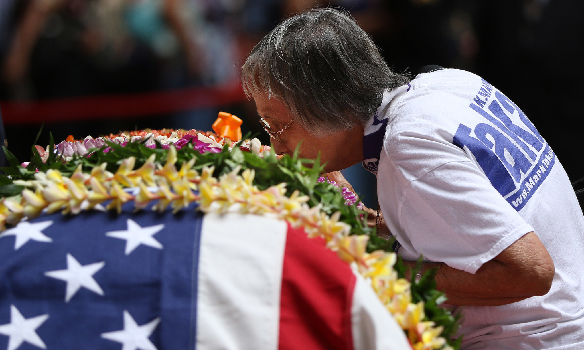 <p>Wearing a Takai campaign shirt, Frances Espiritu kisses Takai&#8217;s casket as she and other supporters and friends say their goodbyes.</p>