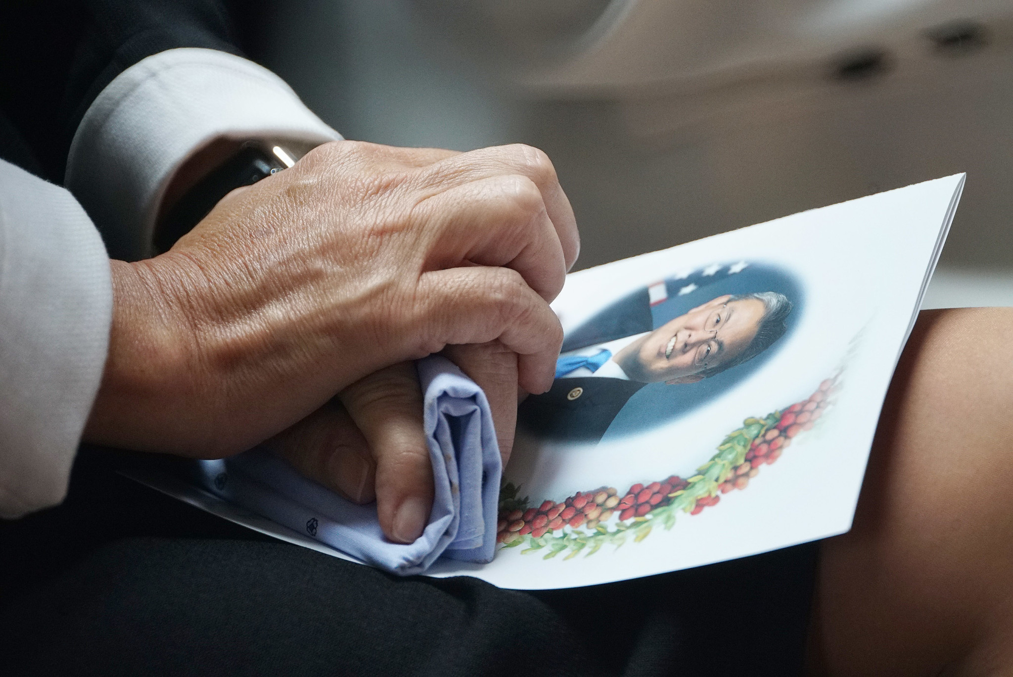 <p>Handkerchief held tightly, a mourner listens as the service draws to a close.</p>