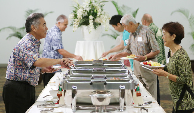 Governor Ige grabs food early and speaks to First Lady Lynn Waihee at the Democratic Party of Hawaii's Unity Breakfast held at the Dole Cannery ballroom. 14 aug 2016