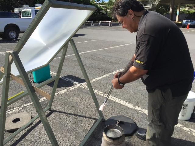 John Cummings III demonstrates the heat potential of the solar cooker.