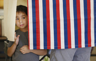 5-year-old Luke Herring peeks out of the polling booth while dad Kevin Herring from downtown votes at Central Middle School cafeteria during primary elections. 13 aug 2016