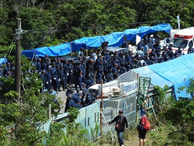 Deep in the Yanbaru Forest hundreds of riot police and protesters face off outside gates and fences surrounding the site of helipads used for US military flight training.