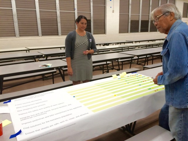 """State Rep. Romy H. Cachola provides his input at an event station. Here attendees are asked to indicate the importance of different development initiatives, like """"Ensure housing affordability"""" or """"New shopping and services."""""""