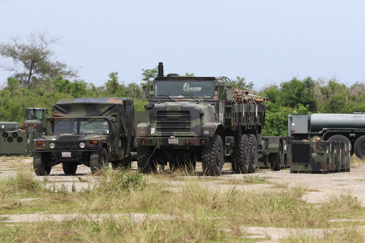 Parked US military trucks and HUMVEEs sits near Runway Abel on Tinian. US Navy seebees assisted with unloading a large cargo ship and then transported many containers to an empty coral field area near the runway on the north of Tinian island. Some of the US Marines there were from Naha, Okinawa. 30 aug 2016