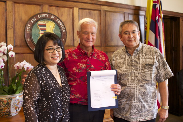 Honolulu Mayor Kirk Caldwell stands in between Haseko Vice President Sharene Tam (left) and Executive Vice President Raymond Kanna (right) after signing bills that allow  Haseko to build a recreational lagoon instead of a marina at the company's Hoakalei development in Ewa.