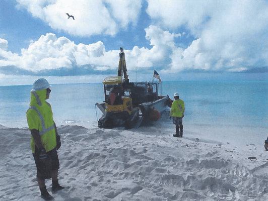 Element Environmental workers load the excavator shortly before the landing craft capsized, Sept. 2, at Kure Atoll.
