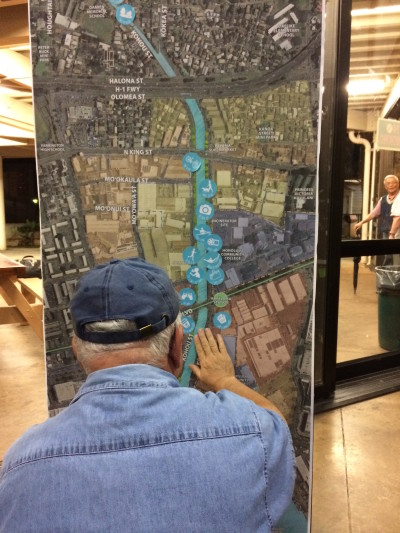 "An attendee at the Kapalama Canal meeting places a sticker of an activity on a map of the canal. Attendees at each table were given stickers with an image and phrase, like ""celebrate culture"""" with a hula dancer, ""bike,"" or ""pau hana"" with an image of two glasses toasting, and instructed to place the sticker on a map of the canal and surrounding area."