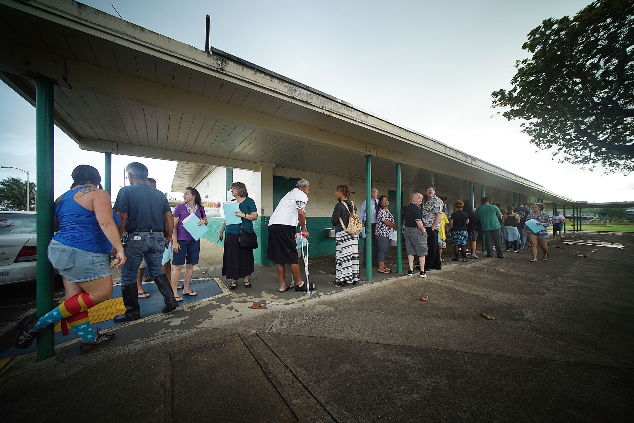 <p>Scores of people queued up to have their paper ballots scanned after voting at Hauula Elementary School. Long lines were common sights at polling places. — Cory Lum/Civil Beat</p>
