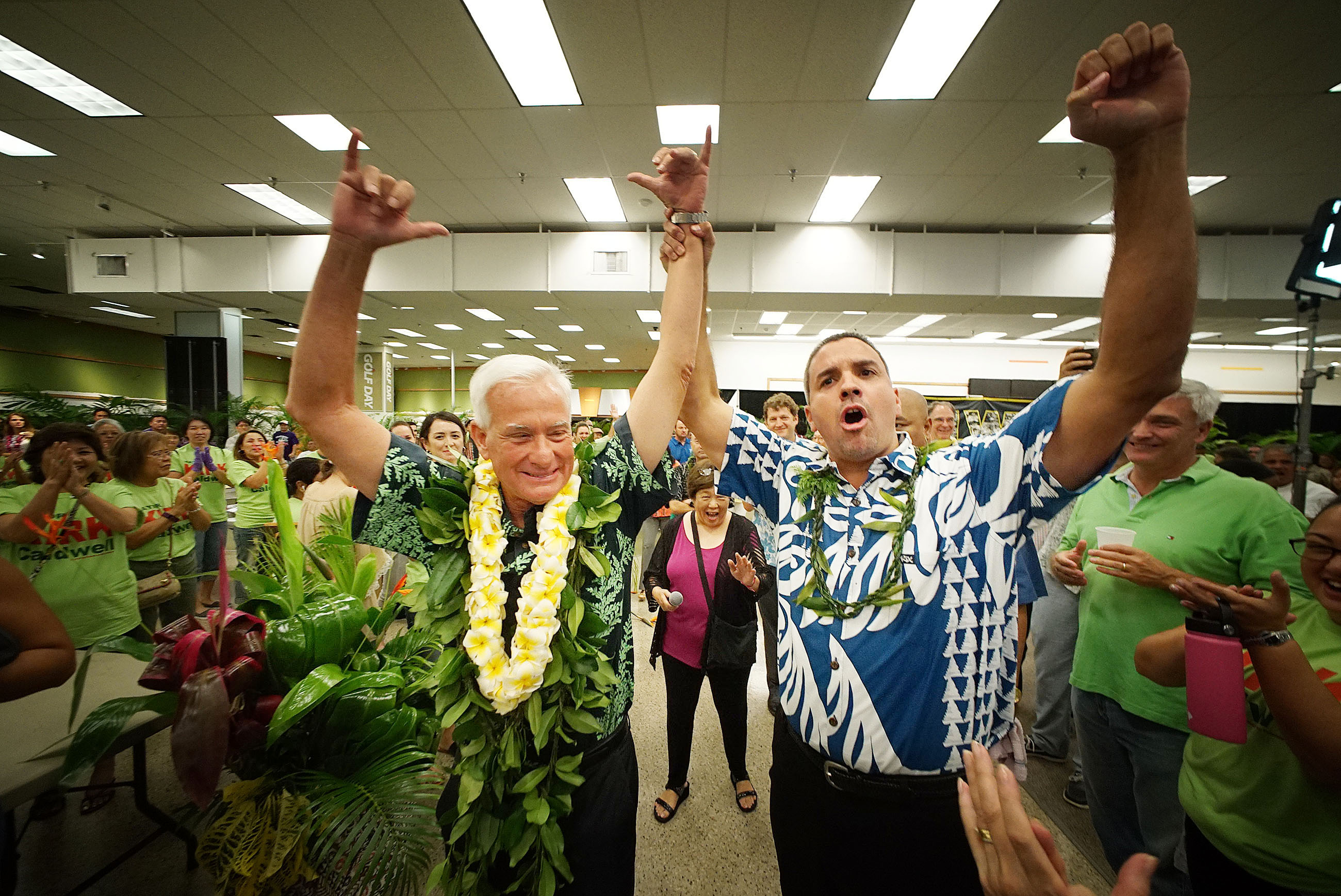 <p>On his way to re-election, Mayor Kirk Caldwell raised arms with City Councilman Ikaika Anderson as returns came in. — Cory Lum/Civil Beat</p>