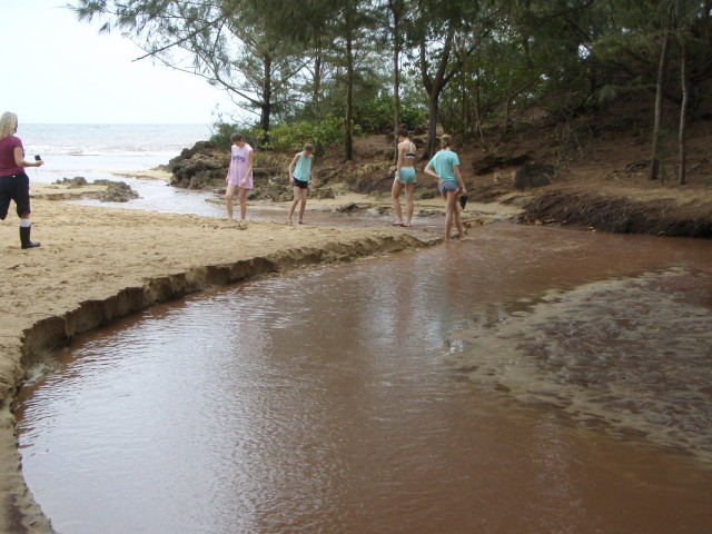 People walk down Waiopili Stream on the south shore of Kauai. The stream regularly exceeds safe levels of wastewater bacteria, sometimes by more than 100 times the recommended limits.