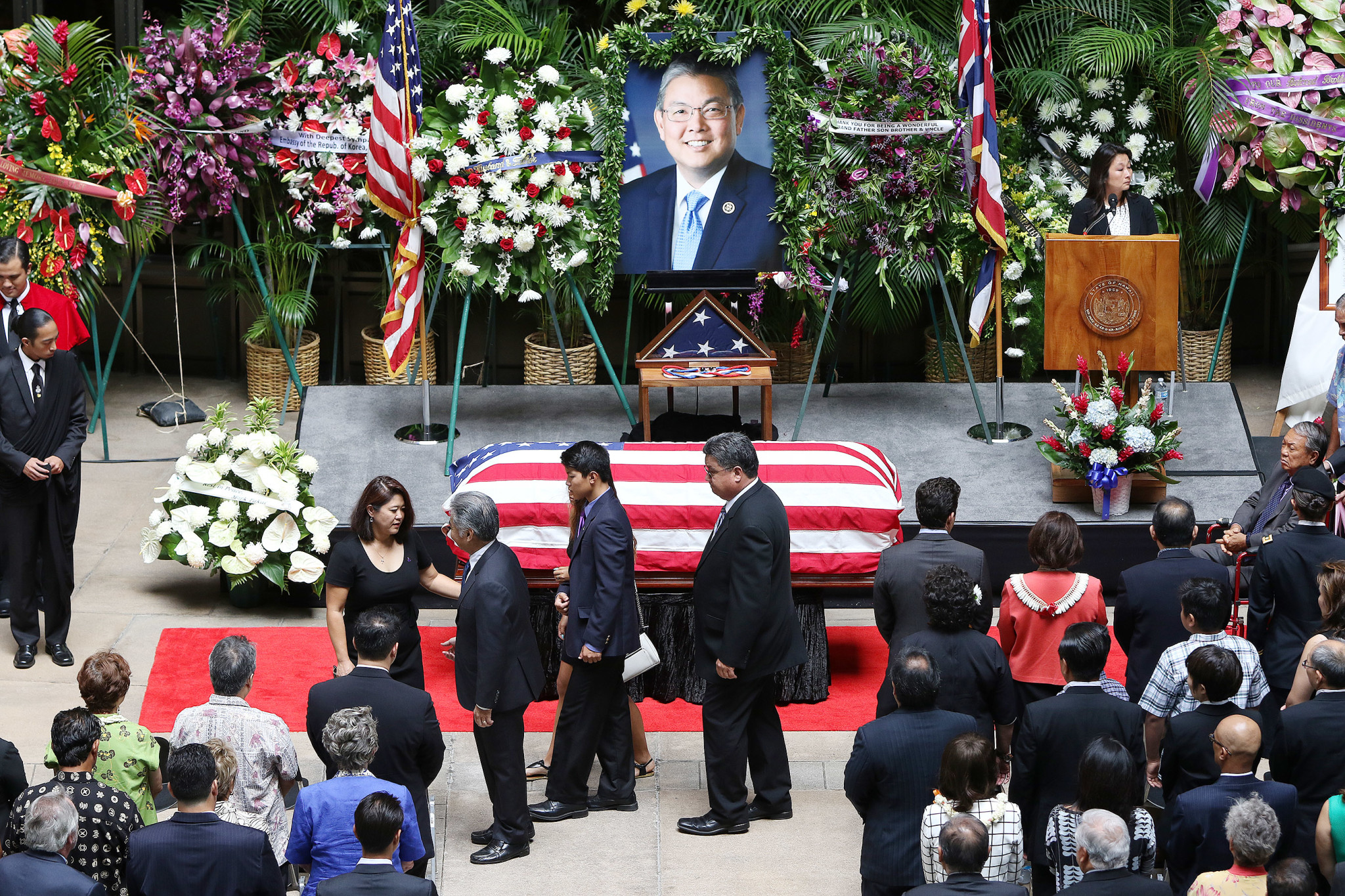 <p>Aug. 18: The late U.S. Rep. Mark Takai&#8217;s  casket rests in the Capitol Rotunda as his wife, Sami, greets Gov. David Ige during a memorial service. After serving 20 years in the state House of Representatives, Takai, 49, was unable to complete his first full term in Congress. <em>Cory Lum/Civil Beat</em></p>