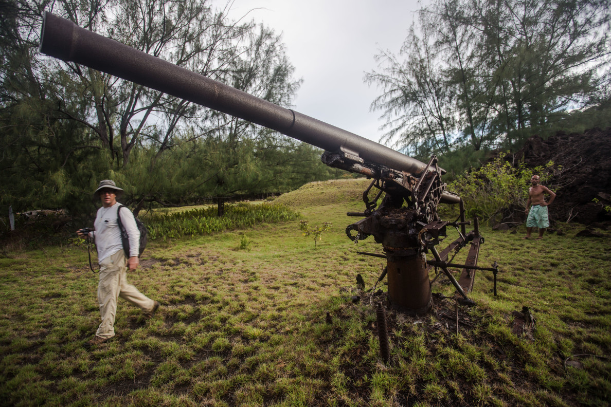 Earthjustice attorney David Henkin, who is suing the Navy, walks by a cannon on Pagan leftover from World War II. Gus Kaipat stands in the background. Kaipat is one of the former residents of Pagan who wants to live there permanently.