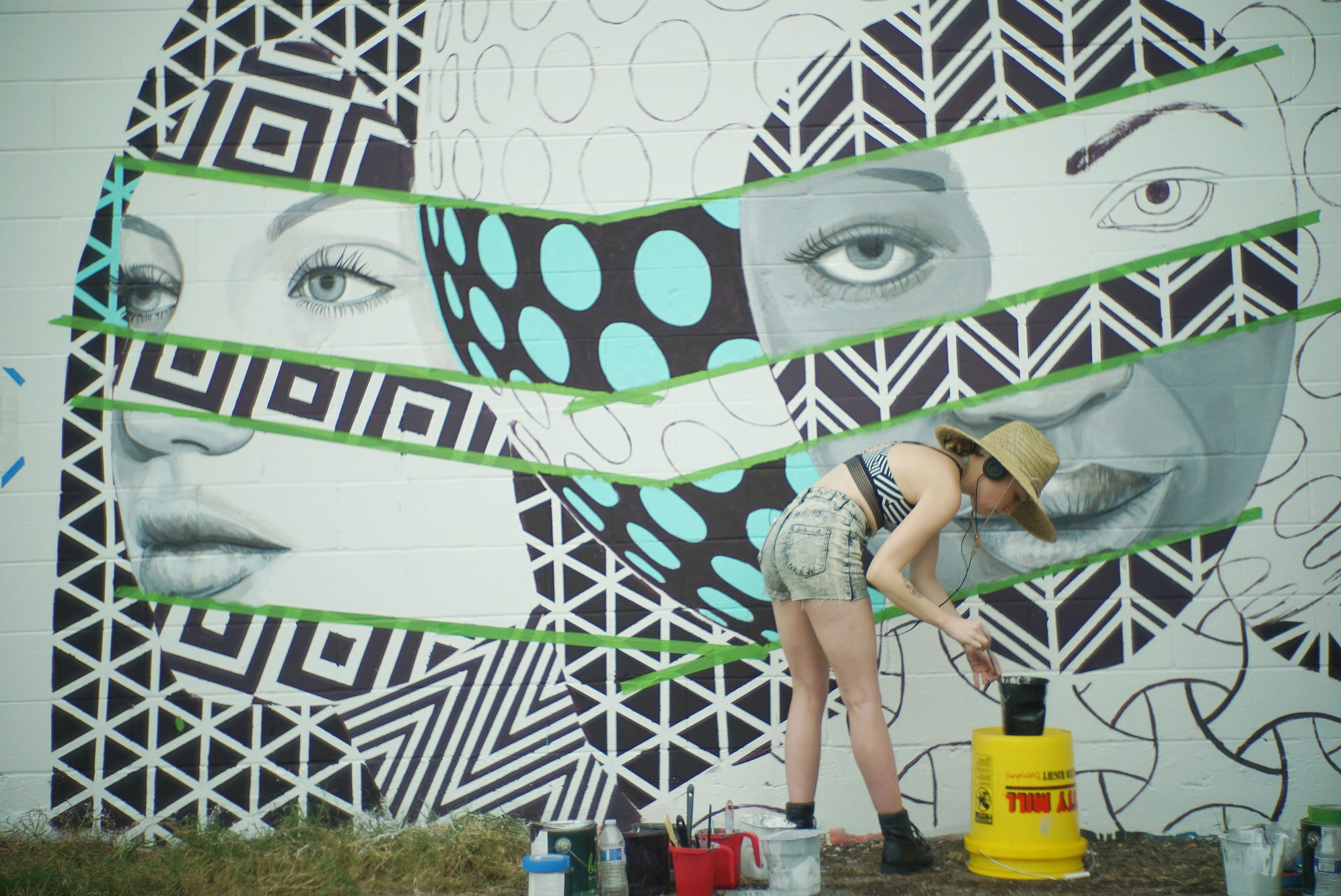 <p>Michelle Tanguay of Detroit works on her mural, &#8220;Love Thy Neighbor,&#8221; along Auahi Street.</p>