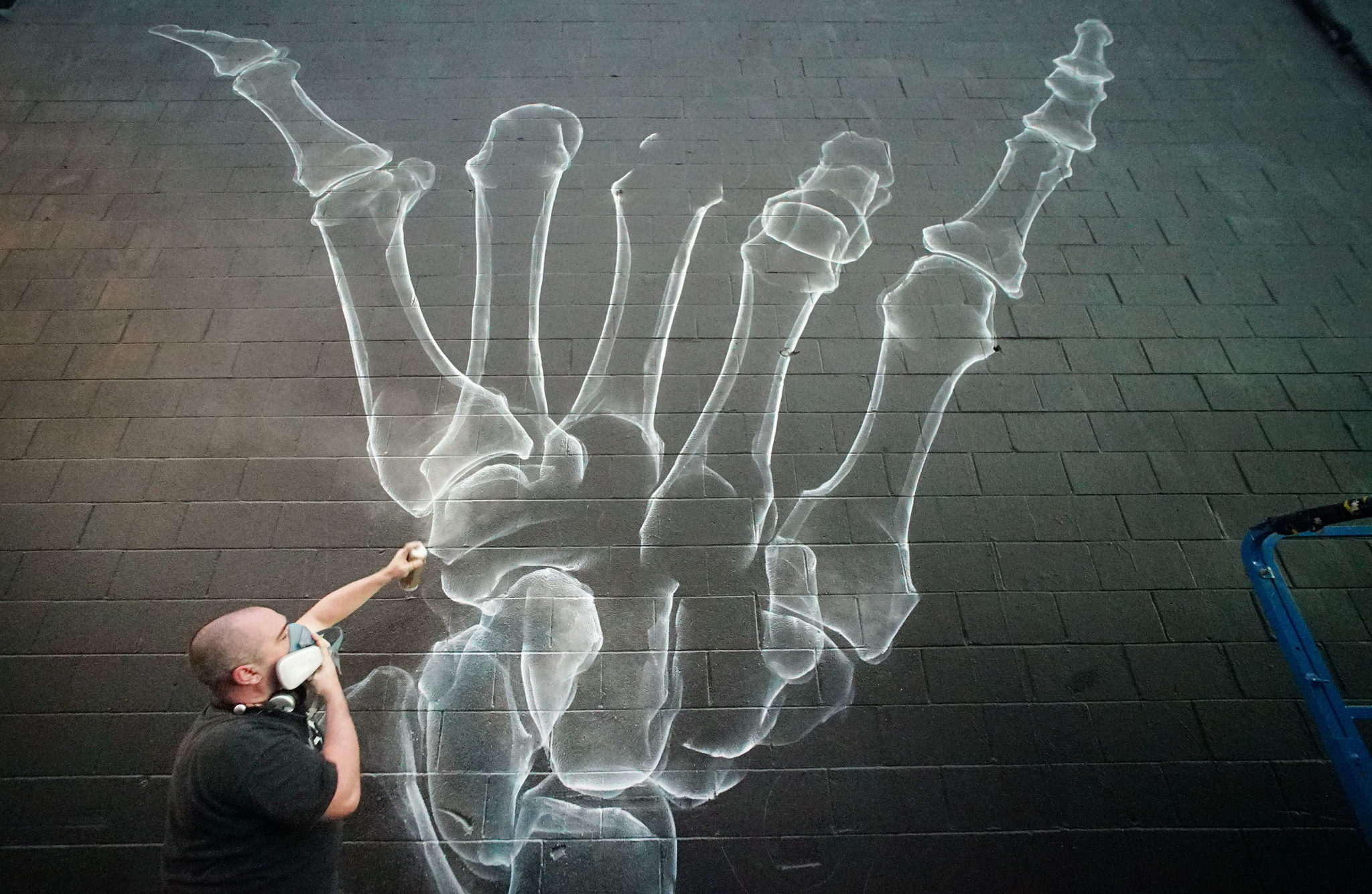 <p>Artist Shok-1 of London spray-paints a skeletal shaka.</p>