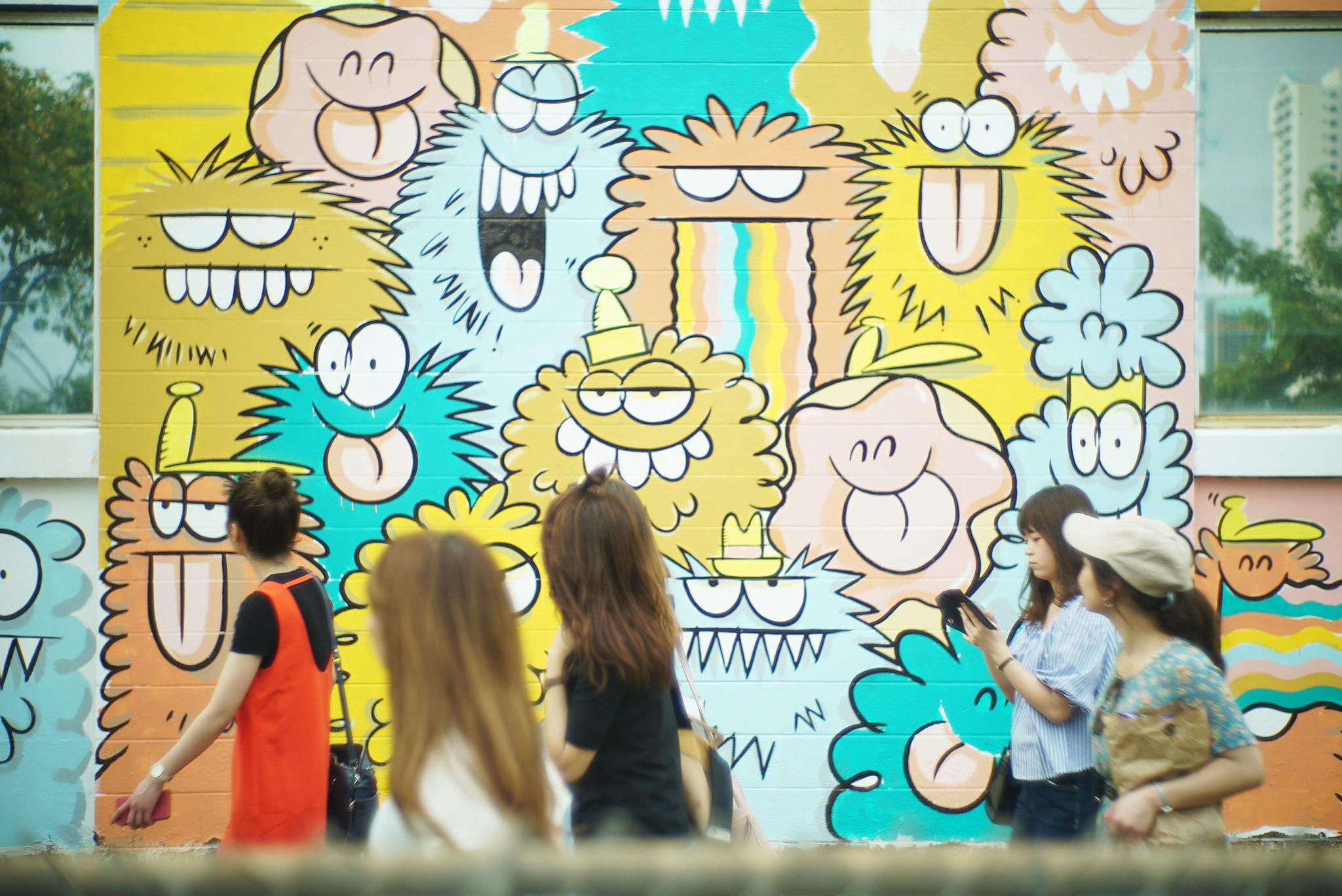 <p>Visitors stroll past Kevin Lyons&#8217; mural in progress.</p>