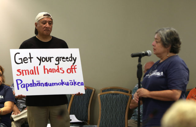 Nathan Yuen holds sign during Fishery Council meeting. Ala Moana Hotel. 21 march 2017