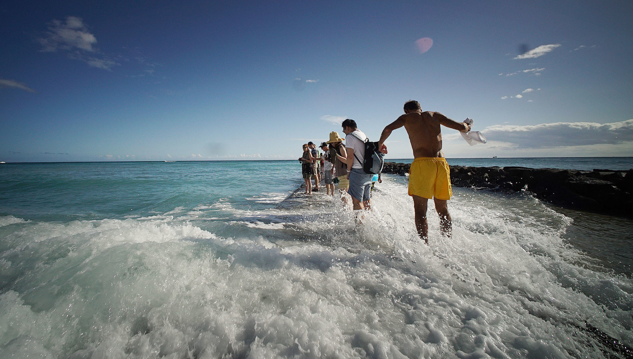 <p>Visitors try to steady themselves as a wave crashes against the concrete walkway Thursday offshore of Fort DeRussy Beach Park.</p>