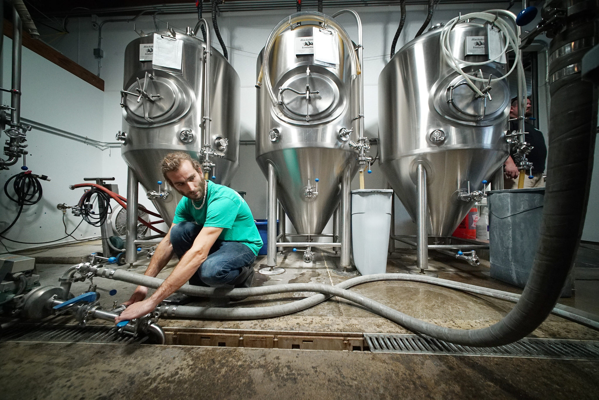 <p>Direnzo flushes and cleans a 15-barrel fermentation tank in preparation for the wort to be piped in.</p>