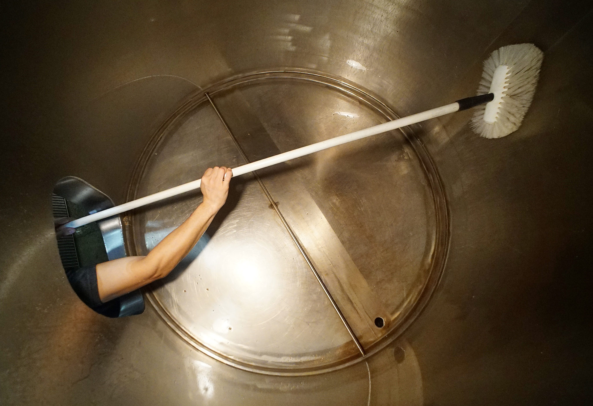 <p>Caldwell uses a long brush to clean the mash tun vessel. Sanitation and cleaning occupies the majority of the brewers&#8217; time.</p>