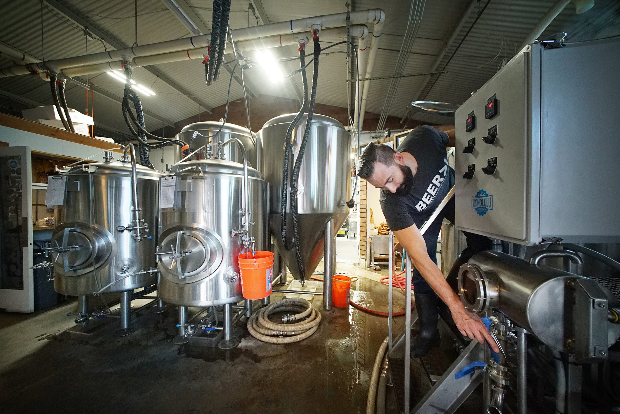 <p>Caldwell makes adjustments to the wort kettle controls before hops are added to the wort.</p>