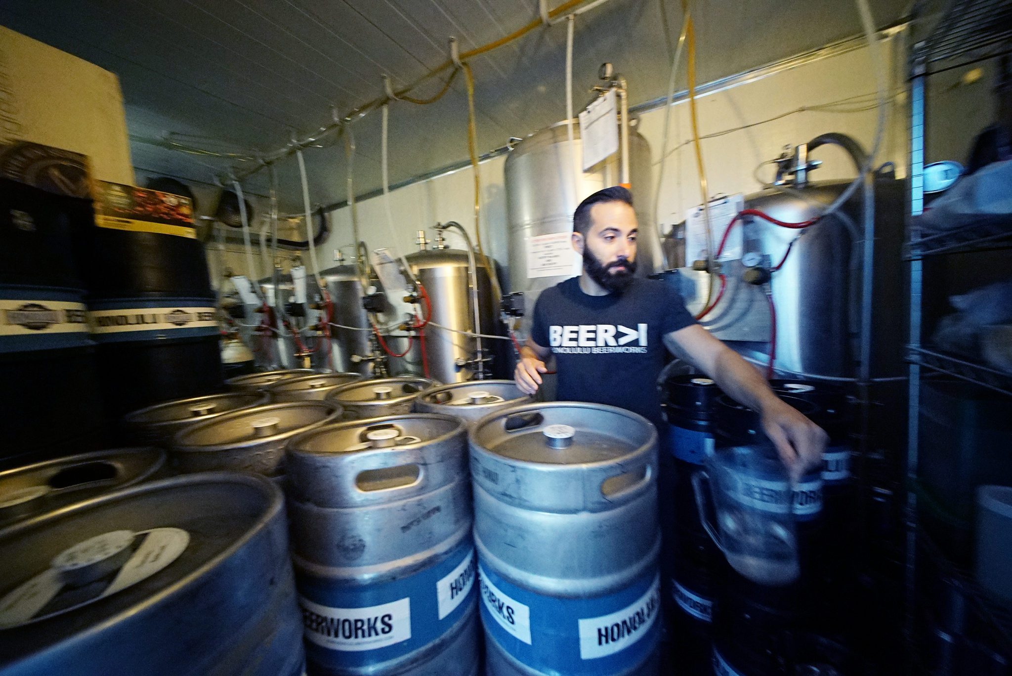 <p>Fifteen-gallon beer kegs are stacked alongside tanks of the finished product.</p>