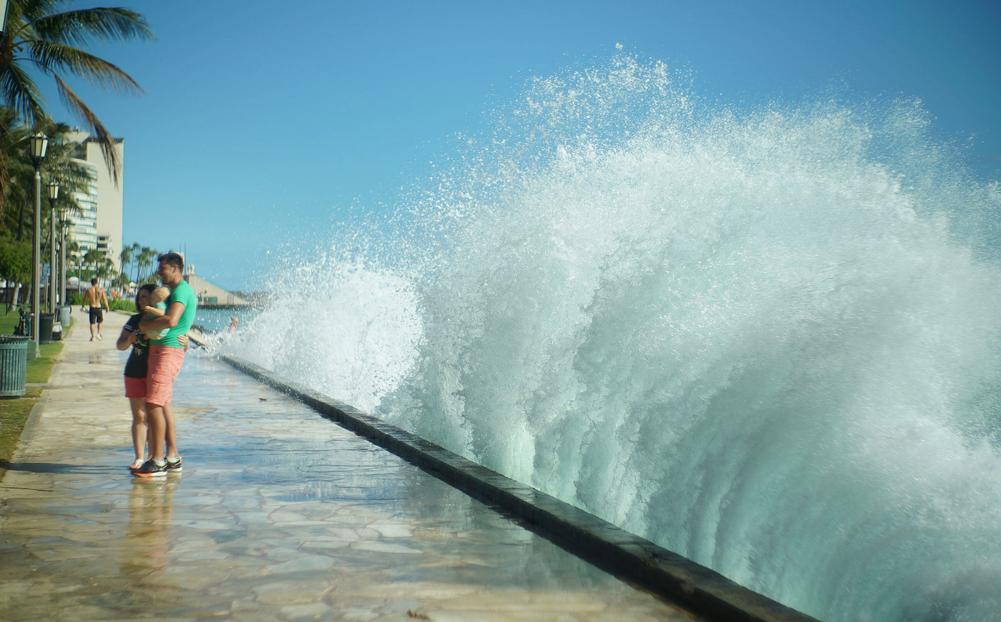 <p>Ivan and Corina Lazarciuc hold their son, Lucas, as a wave crashes Thursday at San Souci State Recreational Park. The family is visiting from Seattle.</p>