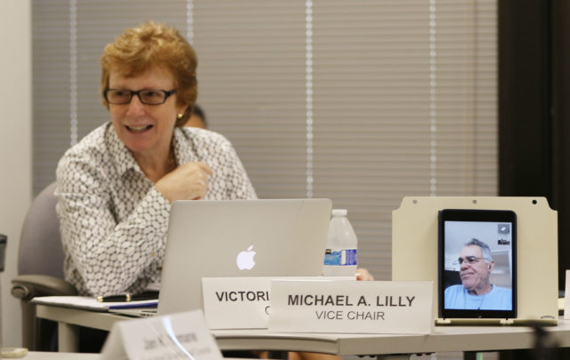 City Ethics Commission vice chair Michael Lilly tunes in live via pad device from Maui with left, Chair Victoria Marks during meeting.
