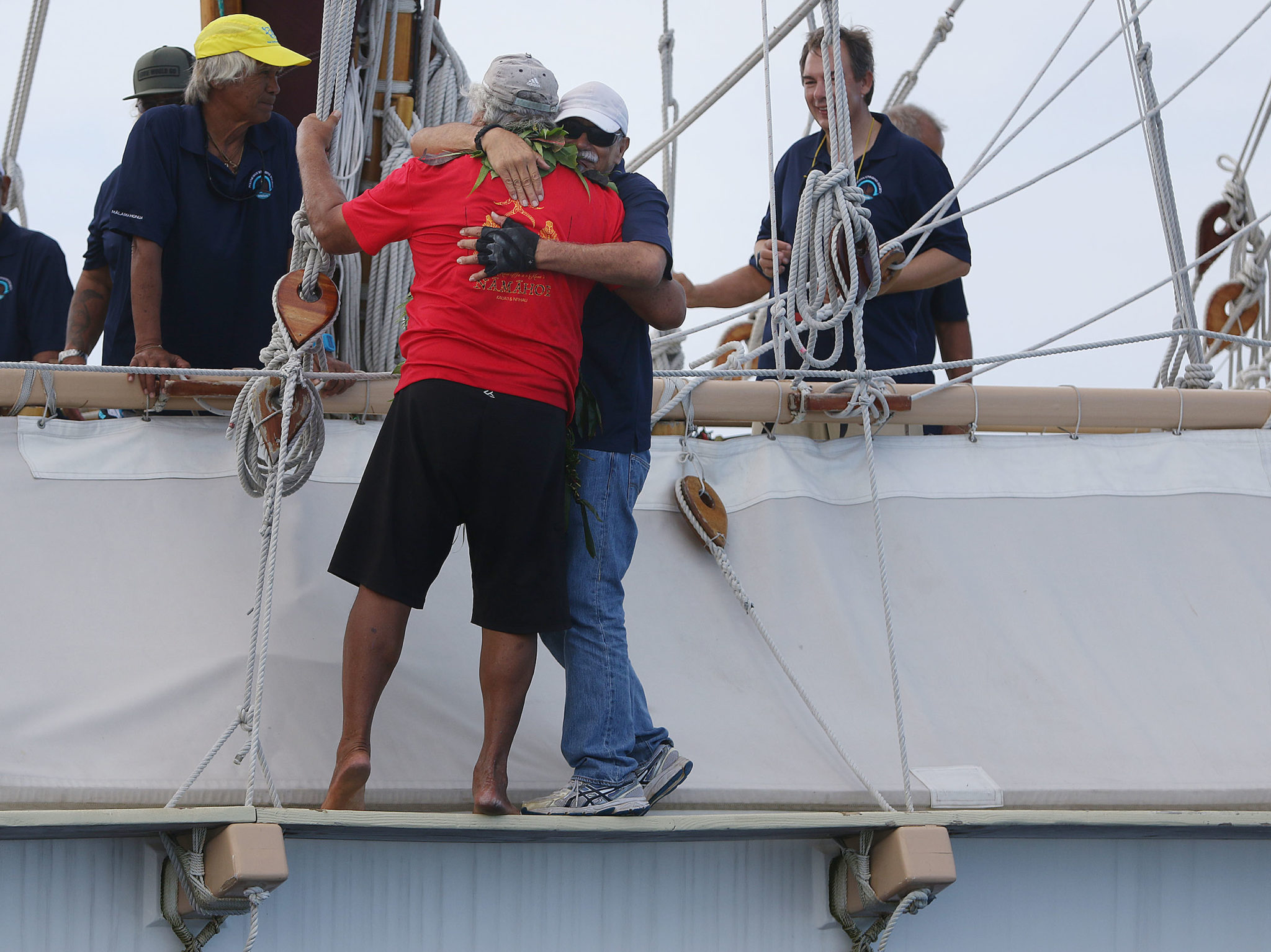 <p>Hokulea skipper Billy Richards, in the white hat, gets a hug as the replica of a Polynesian wa&#8217;a — a double-hulled canoe, approaches shore. / Cory Lum</p>