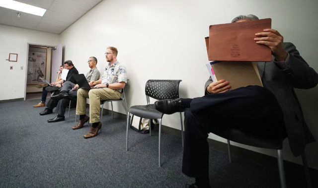 Embattled ex HPD Police Chief Kealhoa's attorney Kevin Sumida hides his face with a folder during HPD Police Commission meeting.