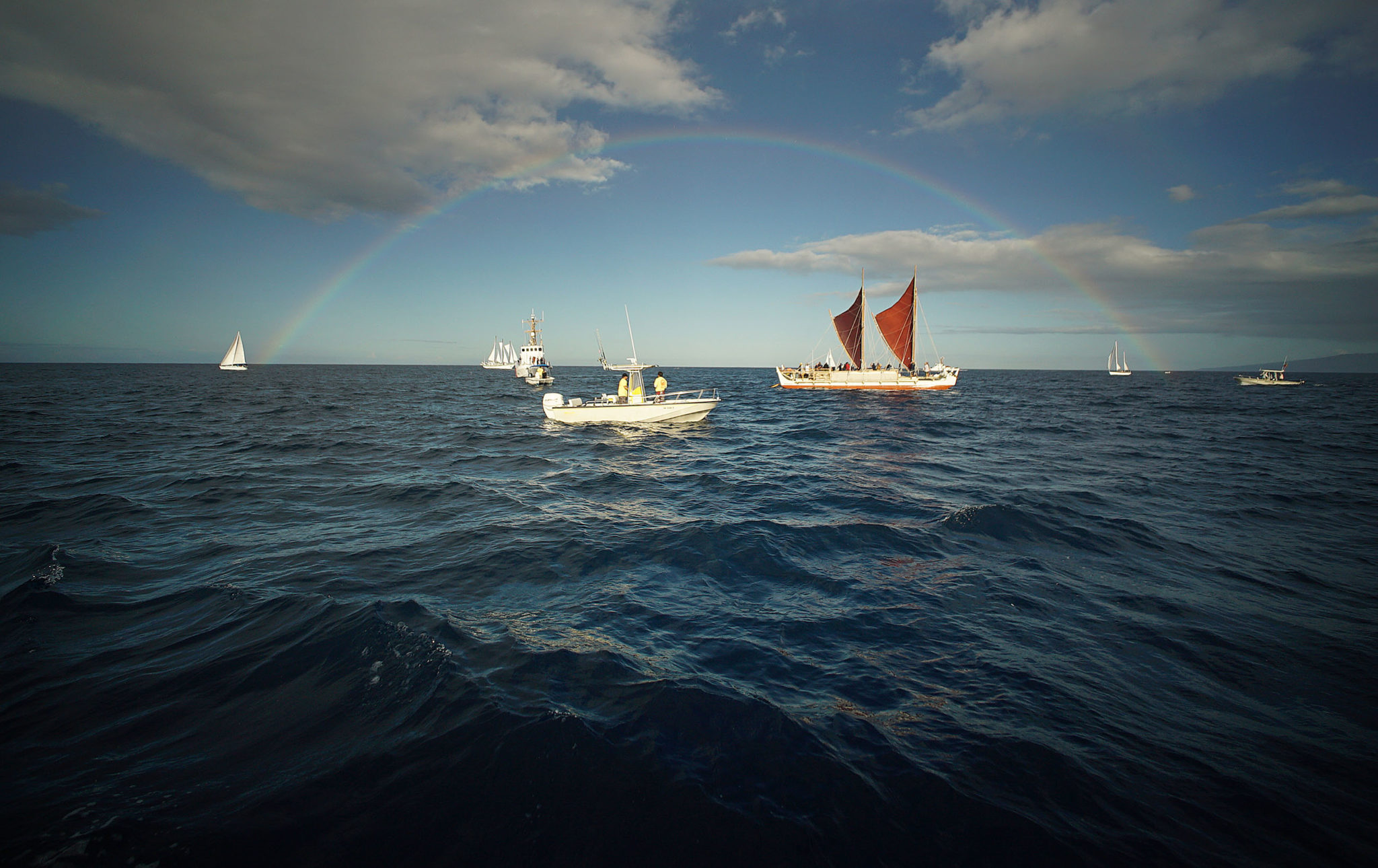 <p>Hokulea sails beneath a rainbow that seems like nature&#8217;s contribution to the welcoming scene. / Cory Lum</p>