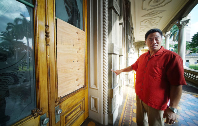 Iolani Palace Executive Director Kippen de Alba Chu points to wood panels that cover the broken glass that someone broke on Sunday. 2 june 2017