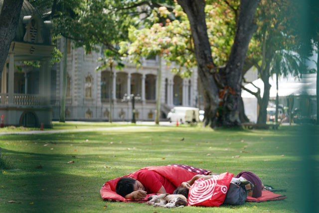 Person sleeps on the Iolani Palace lawn. Denby story interviewed some homeless folks about the recent windows broken on the mauka side of Iolani Palace on sunday. 2 june 2017