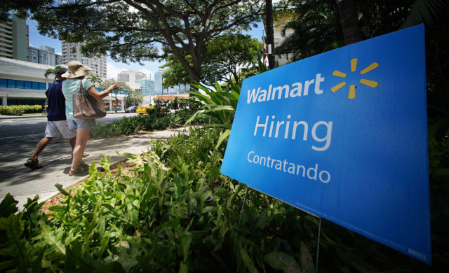 People stroll by on the sidewalk fronting a Walmart hiring sign along Keaaumoku Street.