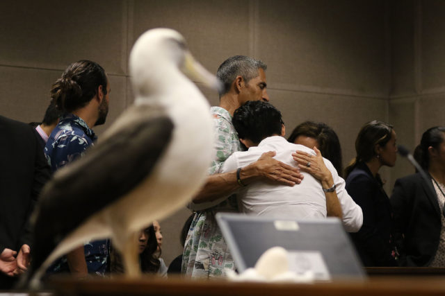 Christian Gutierrez hugs his parents before sentencing during short recess by Judge Jeanette Castagnetti fronting a stuffed Laysan Albatross brought in by the prosecutors office.
