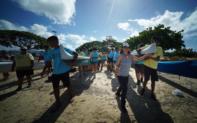 Kehaulani Kupihea directs Waianae students on moving canoe to the water at Sand Island before embarking to Mokauea Island.