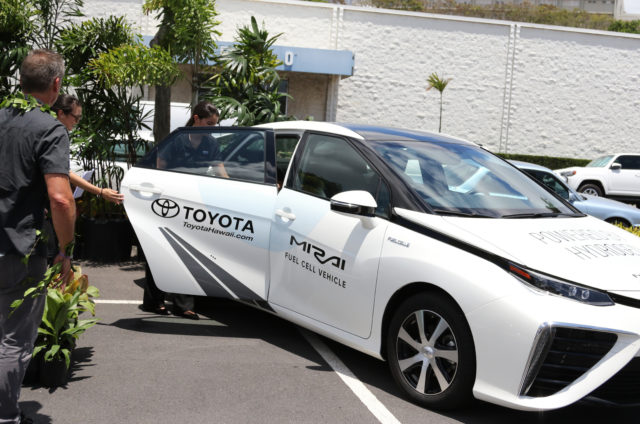 Servco Pacific employees and guests take a look at the hydrogen-powered Toyota Mirai on Wednesday, Aug. 2, 2017 in Honolulu. Servco Pacific is building Hawaii's first public hydrogen fueling station and will begin selling the hydrogen-fueled Toyota Mirai, pictured behind Ige, when the station is complete in early 2018. (AP Photo/Cathy Bussewitz)