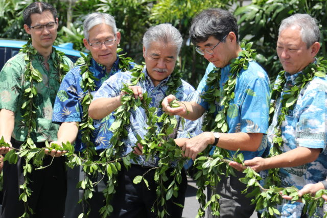 Hawaii Gov. David Ige, center, and Mark Fukunaga, chairman and CEO of Servco Pacific, second from right, and others hold a maile lei during a groundbreaking ceremony for Hawaii's first public hydrogen fueling station on Wednesday, Aug. 2, 2017, in Honolulu. Servco Pacific is building the station and will begin selling the hydrogen-fueled Toyota Mirai when the station is complete in early 2018. (AP Photo/Cathy Bussewitz)