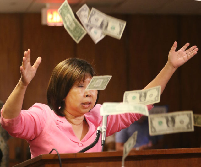After testifying during WAM hearing Choon James tosses a hand full of dollar bills into the air at the Capitol auditorium.