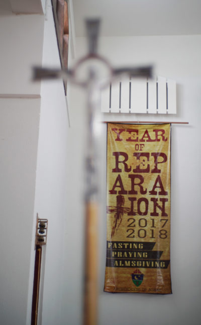 Cross located inside Mount Carmel Church in Hagat, Guam. Church that former Father Anthony Apuron allegely sexually abused Roy Quintanilla and Roland Sandia. Year of Reparation 2017 2017 banner.