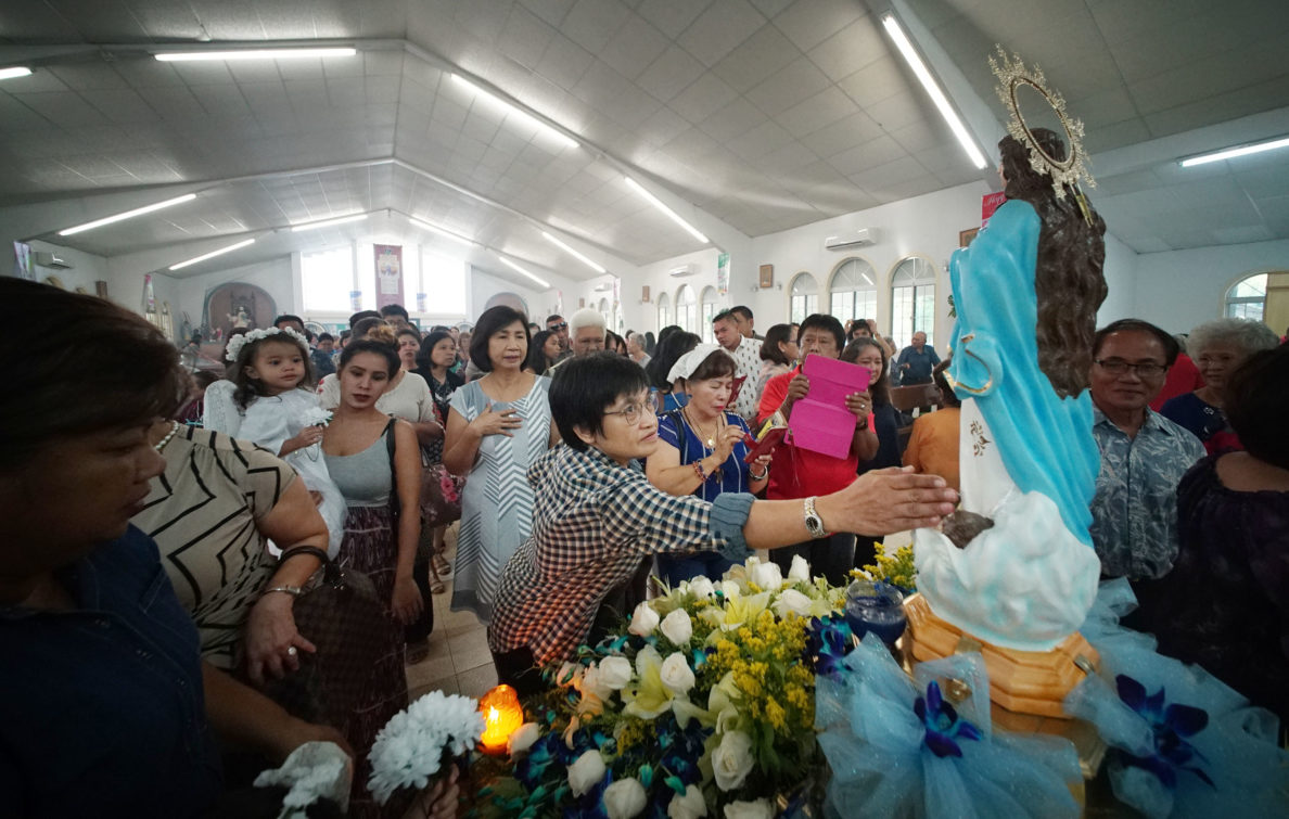 Parishioners pay their respects during mass/celebration held at Assumption of Our Lady in Piti, Guam.