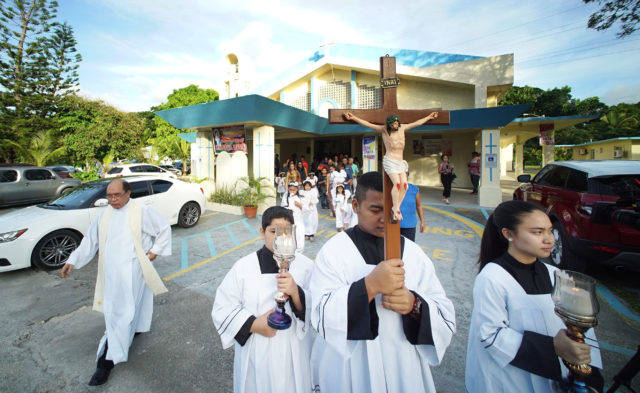 Left, Father Mel Camina leads processional out of the Assumption of Our Lady in Piti, Guam during processional.