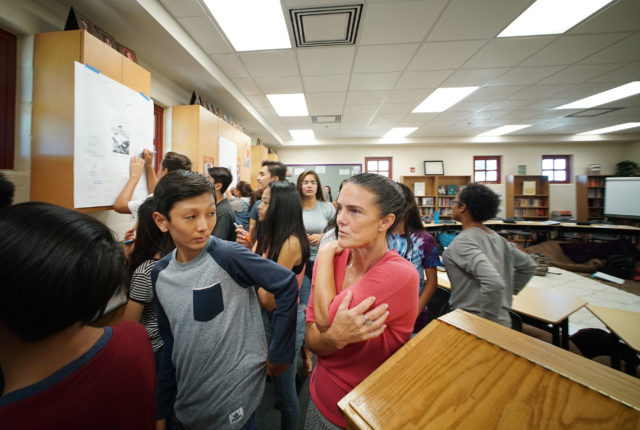 Mrs. Amy Perruso walks around her class of 9th grade students as they quietly write observations on two Bayonet Constitution political cartoons from 1887 in her Mililani High School class.
